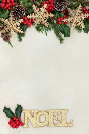 Christmas and noel background border with gold glitter sign and snowflake bauble decorations, holly, fir and cedar cypress greenery on parchment paper. Stock Photo