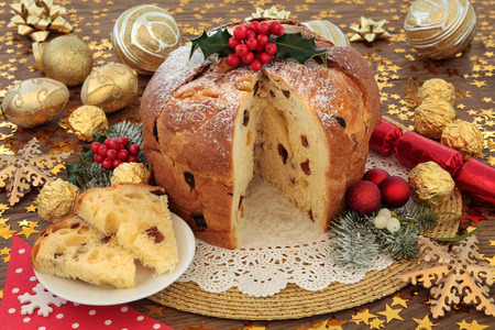 Italian panettone christmas cake and slice with red and gold bauble decorations, holly and winter flora over oak background with stars. Stock Photo