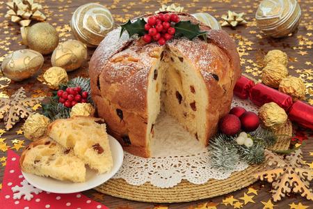 CAKE: Panettone pastel de Navidad italiano y rebanada con adornos de color rojo y la chuchería de oro, el acebo y la flora de invierno sobre fondo de madera de roble con las estrellas.