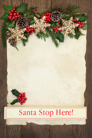 christmas fun: Letter to santa with sign, with gold christmas snowflake bauble decorations, holly and winter greenery on parchment paper over oak background. Stock Photo
