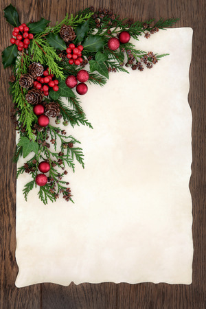 christmas ivy: Christmas abstract background border with red bauble decorations, holly, ivy, cedar cypress and fir on parchment paper over old oak wood. Stock Photo