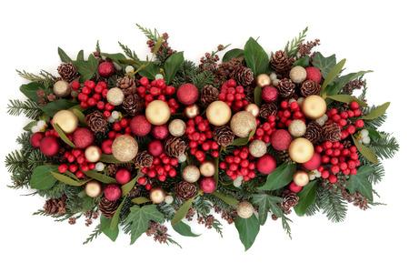 muerdago: Navidad Decoraciones de la chucher�a roja y oro, acebo, el mu�rdago, la hiedra, pi�as de pino y vegetaci�n tradicional sobre fondo blanco.