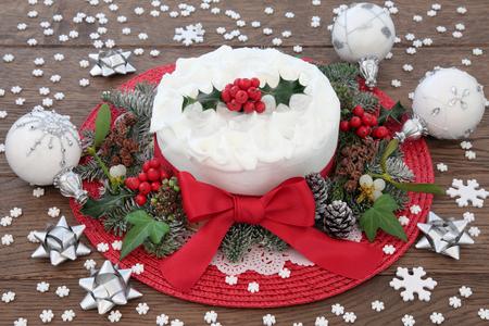 weihnachtskuchen: Weihnachtskuchen mit Holly, Baumschmuck Dekorationen und Wintergrün über Eiche Hintergrund.