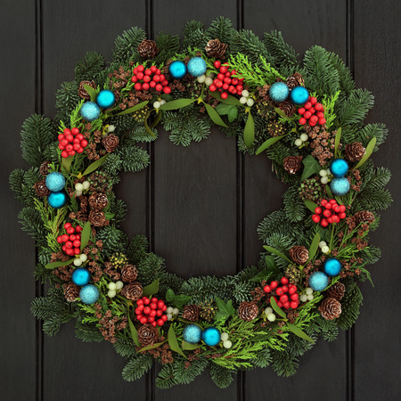 green door: Christmas wreath with blue bauble decorations, holly, mistletoe, pine cones and blue spruce fir over dark blue oak front door background. Stock Photo