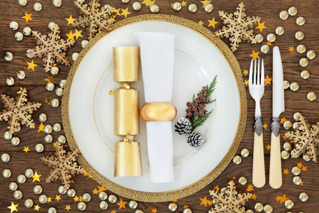 christmas cracker: Christmas holiday dinner place setting with plates, napkin, cutlery, gold bauble decorations over oak table background. Stock Photo