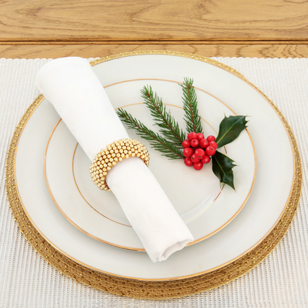 napkin ring: Christmas dinner place setting with plates, napkin and gold ring, holly and fir on a silver table runner over oak background.