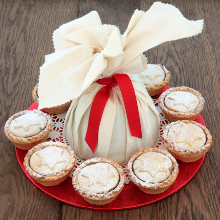 doiley: Christmas pudding in a muslin bag with mince pies over oak background.