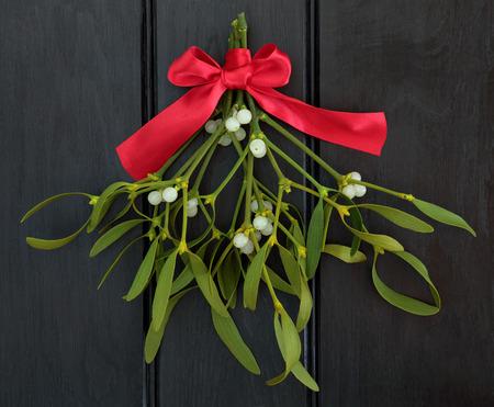 muerdago: Muérdago de Navidad con lazo de cinta roja sobre fondo de madera oscura. Foto de archivo
