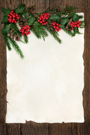 old fashioned christmas: Christmas abstract background border with holly, ivy, cedar cypress and fir on parchment paper over old oak wood.