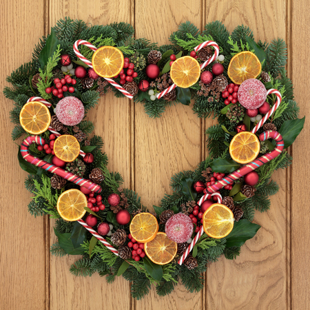 Christmas heart shaped wreath with dried fruit, candy canes, bauble decorations, holly, mistletoe and greenery over oak front door background.