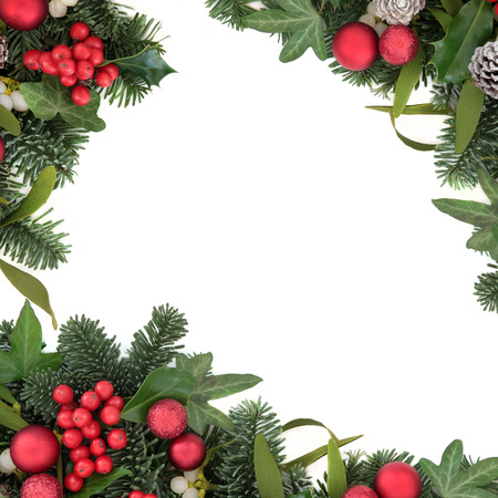 christmas ivy: Christmas background border with holly, red bauble decorations, ivy, mistletoe, snow covered pine cones and blue spruce fir over white. Stock Photo