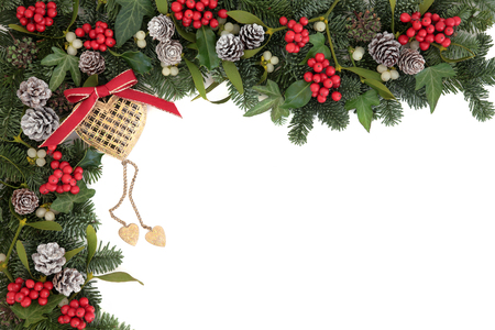 christmas ivy: Christmas abstract background border with gold heart bauble decoration, holly, ivy, mistletoe, pine cones and blue spruce fir over white. Stock Photo