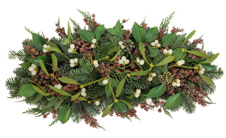 arrangements: Mistletoe and winter greenery of ivy, blue spruce and cedar cypress leyland leaves with pine cones over white background.