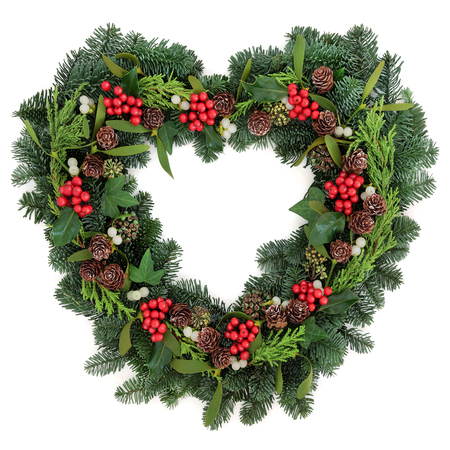 christmas ivy: Christmas heart shaped wreath with holly mistletoe, ivy, pine cones and winter greenery over white background. Stock Photo