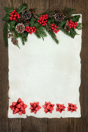 christmas border: Christmas abstract background border with red ribbon decorations, holly, ivy, cedar cypress and fir on parchment paper over old oak wood.