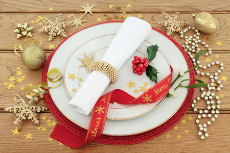 christmas meal: Christmas dinner still life with place setting, plates, napkin, ribbon, holly, mistletoe and gold baubles with stars over oak background.