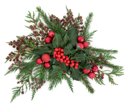 Centrepiece: Christmas and winter flora with red bauble decorations, holly, ivy, fir and cedar cypress over white background. Stock Photo