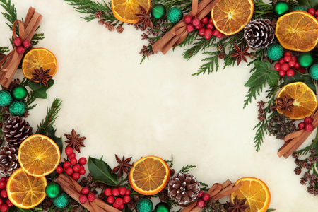 Christmas background border with dried fruit and spices, green bauble decorations, holly and winter greenery over old parchment paper. Stock Photo