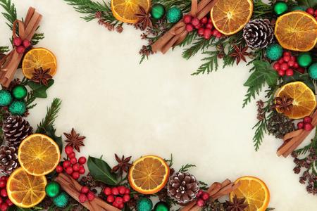 frutas deshidratadas: Frontera del fondo de Navidad con frutos secos y especias, verde Decoraciones de la chuchería, el acebo y el verdor del invierno sobre el papel de pergamino antiguo. Foto de archivo