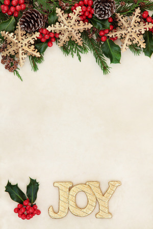 old fashioned christmas: Christmas background border with gold joy sign, snowflake bauble decorations, holly and winter greenery over old parchment paper. Stock Photo