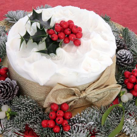 weihnachtskuchen: Weihnachtskuchen mit Stechpalme, Mistel und Winter viel Gr�n auf rotem Hintergrund.