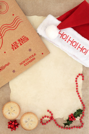 mince pie: Christmas eve letter to santa with ho ho ho red hat, mince pie cakes, parcel package and decorations over parchment and brown paper background. Stock Photo