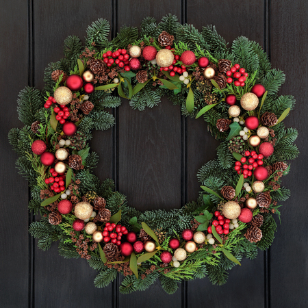 christmas decorations: Christmas wreath with red and gold bauble decorations, bow, holly, mistletoe, pine cones and blue spruce fir over dark oak front door background.
