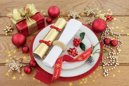 place setting: Christmas dinner place setting with plates, napkin, ribbon, gift box, baubles, cracker, holly and mistletoe over oak background.