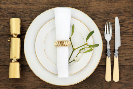 traditional christmas dinner: Christmas holiday dinner place setting with plates, napkin, cutlery and mistletoe over old oak table background. Stock Photo