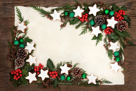 christmas ivy: Christmas background border with gingerbread cookies green bauble decorations, holly, ivy, fir and pine cones on parchment paper over old oak wood.