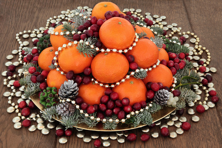 satsuma: Christmas satsuma orange and cranberry fruit, gold bead and smartie decorations, holly, mistletoe and winter greenery over oak background. Stock Photo