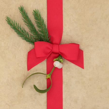 christmas present box: Christmas gift wrapping with red ribbon and bow, mistletoe and fir over hemp paper background.