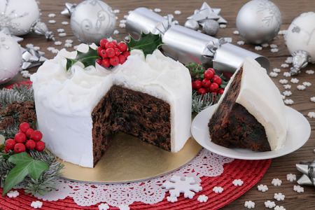 Christmas cake and slice with holly, bauble decorations and winter greenery over oak background.