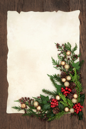 christmas paper: Christmas abstract background border with gold bauble decorations, holly, ivy, cedar cypress and fir on parchment paper over old oak wood.