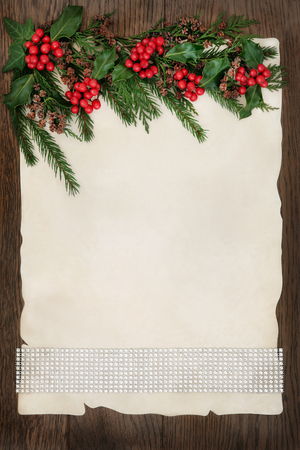 christmas ivy: Christmas abstract background border with diamond ribbon, holly, ivy, cedar cypress and fir on parchment paper over old oak wood. Stock Photo