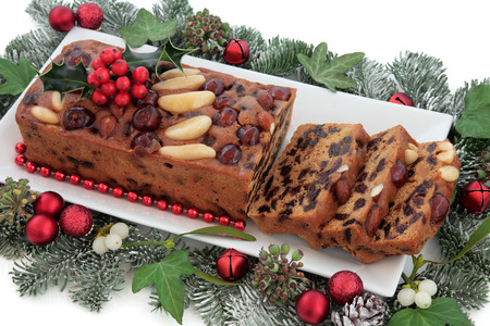 fruitcake: Genoa cake with holly, red bauble christmas decorations and winter greenery on a porcelain plate over white background.