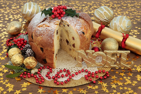 Panettone christmas cake with red and gold bauble decorations, noel sign, holly and winter flora over oak background with stars.
