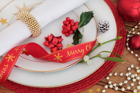traditional christmas dinner: Christmas dinner place setting with plates, napkin, ribbon, holly and mistletoe with red baubles over oak background.