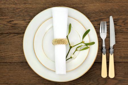 접시, 칼 붙이, 냅킨 및 미 슬 토 오래 된 오크 테이블 배경 위에 크리스마스 저녁 식사 테이블 설정입니다. 스톡 콘텐츠