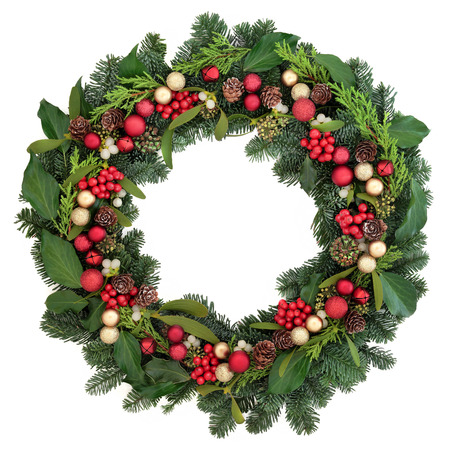 pine wreath: Christmas wreath with red bauble decorations, holly, ivy, mistletoe and winter greenery over white background. Stock Photo