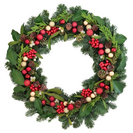 corona de adviento: Corona de Navidad con decoraciones chuchería rojo, acebo, hiedra, muérdago y zonas verdes de invierno sobre fondo blanco.