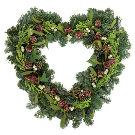 christmas ivy: Christmas heart shaped wreath with mistletoe, ivy, pine cones and winter greenery over white background. Stock Photo