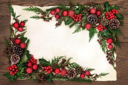 old fashioned christmas: Christmas background border with red bauble decorations, holly, ivy, fir and cedar cypress greenery on parchment paper over old oak wood.
