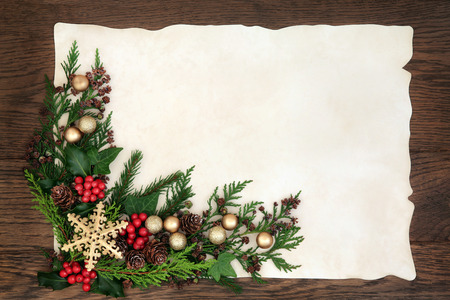 ivy: Christmas abstract background border with snowflake bauble decorations, holly, ivy and fir on parchment paper over old oak wood.