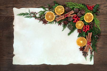 spices: Christmas abstract background border with dried fruit and spice, holly, ivy, cedar cypress and fir on parchment paper over old oak wood.