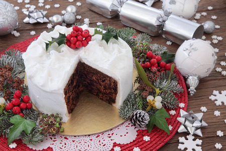 dundee: Traditional christmas cake with holly, bauble decorations and winter greenery over oak background.