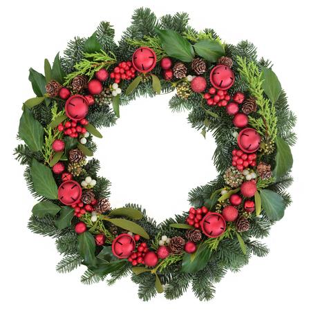 muerdago: Corona de Navidad con decoraciones chucher�a rojo, acebo, hiedra, mu�rdago y zonas verdes de invierno sobre fondo blanco.
