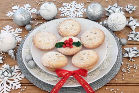 carne picada: Pasteles de carne, cinta Feliz Navidad, decoraciones de la chuchería y el acebo sobre fondo de roble.