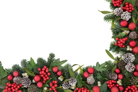 Frontera del fondo de Navidad con las decoraciones de la chuchería, acebo, hiedra, muérdago, piñas de pino y el abeto azul sobre blanco.