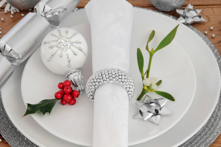 traditional christmas dinner: Christmas holiday dinner place setting with plates, napkin,  bauble decorations, holly and mistletoe over oak background.